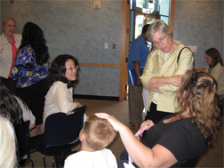 In Seattle, Representative Ruth Kagi (D-Shoreline) talks with a mother and her child, along with Janice Deguchi of the Denise Louie Education Center, at a Department of Early Learning Subsidy Rules Hearing.