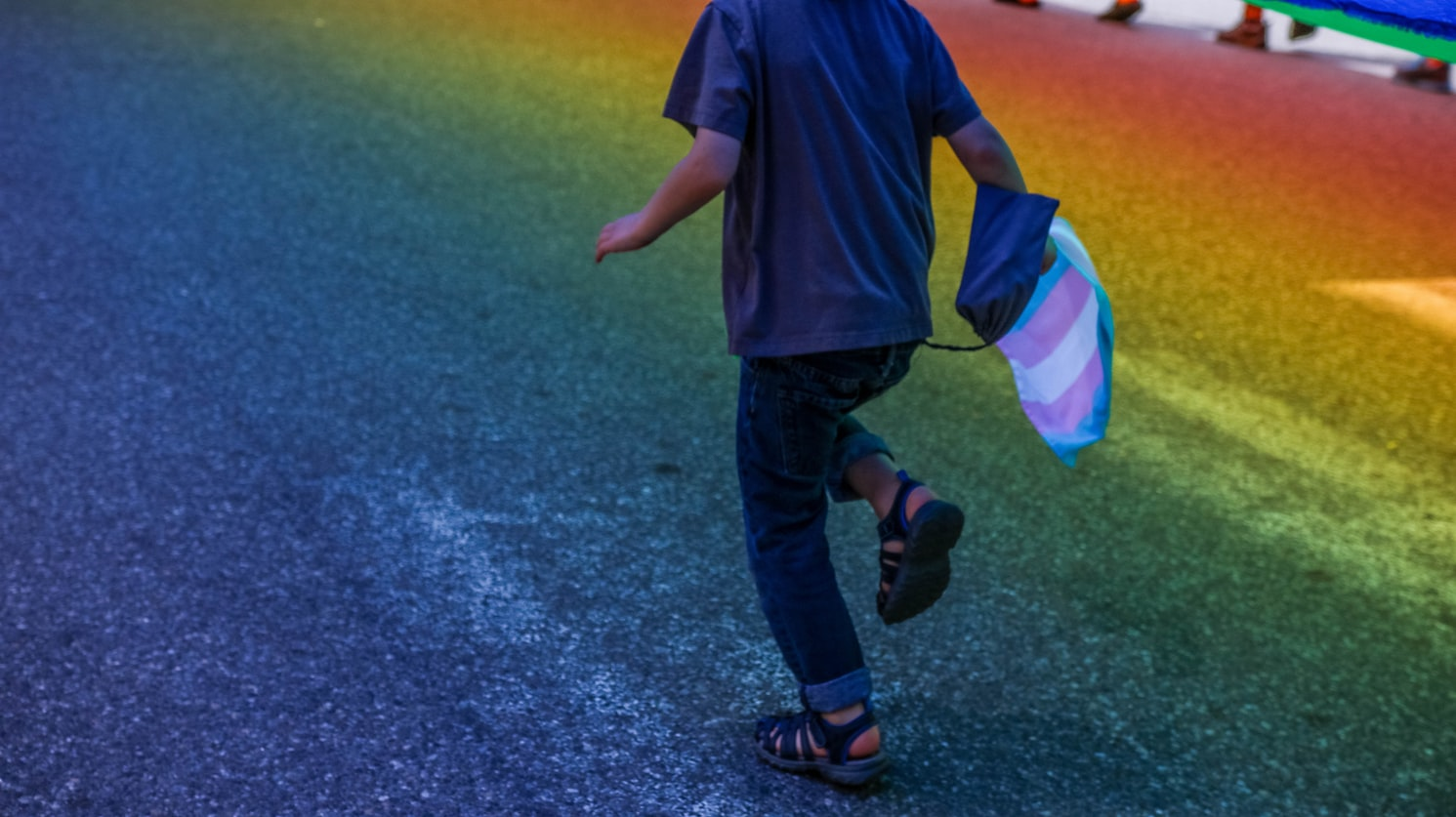 A child is running with a flag in their hand