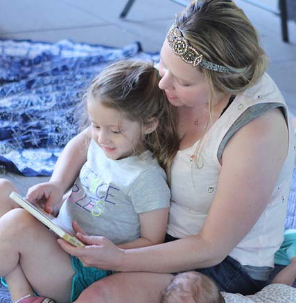 Adult and child sitting together reading a book