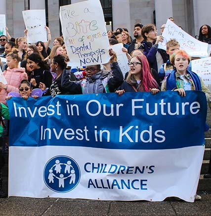 Children holding a Children's Alliance banner