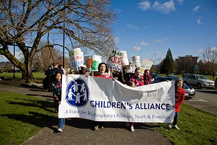 Kids marching with a Children's Alliance banner